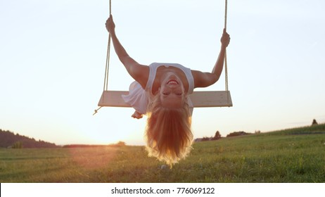 LENS FLARE CLOSE UP: Lovely young lady's blonde locks flow gently in sunlit countryside as she swings on rope swing under tree. Smiling woman with red lips leans back on swing on beautiful afternoon.