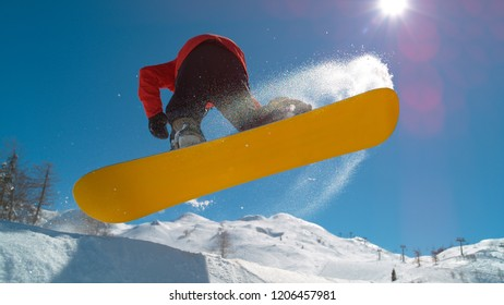 LENS FLARE, CLOSE UP: Pro snowboarder rides up to the edge of the kicker and jumps in the air to do an awesome trick. Athletic male tourist snowboarding starts to spin as he takes off in the air.