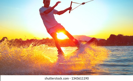 LENS FLARE CLOSE UP: Surfer wakeboarding an jumping ollie at golden sunset. Skilled wakeboarder doing ollie jump, splashing water drops into the camera. Young man riding cable wake park on vacation