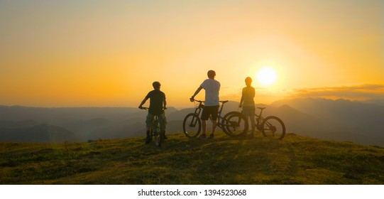 LENS FLARE, COPY SPACE: Group of unrecognizable fit tourists on bicycles observes the golden sunrise in tranquil Slovenian mountains. Three friends observe the sunset after cross country biking trip