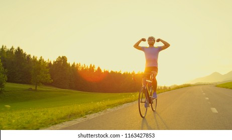 LENS FLARE, COPY SPACE: Triumphant road biker happy to finish challenging race in golden-lit nature. Biker lets go of handlebars and outstretches his arms to celebrate his win in road cycling race.