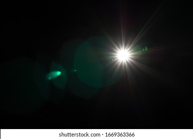 Lens Flare effect close up. Different colors (green, red, white, yellow) light over black background. Abstract sun burst. Easy to add overlay or screen filter over photos and images. Copy space.