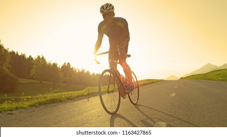 LENS FLARE: Intense male biker pedals his road bicycle on a summer sunny evening. Young sportsman riding his bike during a difficult cycling race through the spring countryside. Man sprinting on bike.