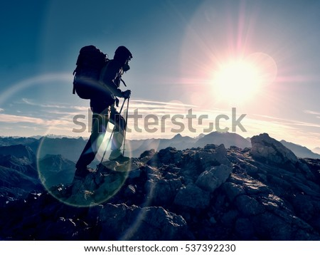 Lens flare light, strong defect. Tourist guide on trekking path  with poles and backpack.  Experienced hiker in windcheater and hood stand on rocky view point above misty valley. Sunny fall day