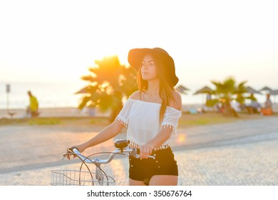 Lens flare photo of amazing lady wearing black floppy hat biking in sun flare on seaside background