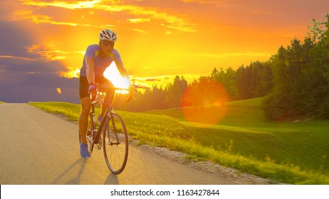 LENS FLARE: Sporty cyclist on road bike training on a sunny day in pretty green nature. Athletically built Caucasian male with sunglasses rides his road bicycle through beautiful spring landscape.