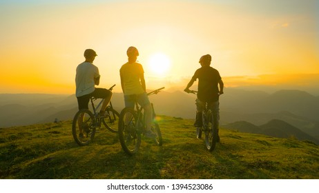 LENS FLARE: Unrecognizable sporty tourists rest on bicycles and observe the picturesque summer sunrise before a downhill biking adventure in the scenic Slovenian mountains. Cyclists observe sunset.