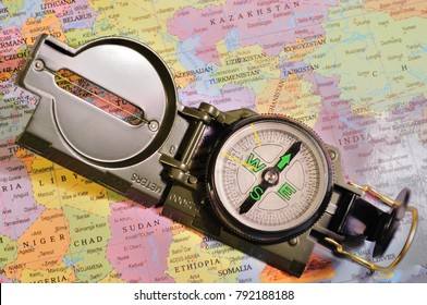 A lensatic compass against a world map. The maps are generic versions and do not have copyrights.