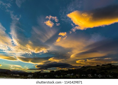 Lenticular clouds illuminated by the sun shine in the sky. Stunning sunset on the Pacific coast, New Zealand. The concept of active and ecotourism