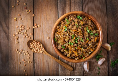 Lentil with carrot and onion in a wooden bowl. Healthy lifestyle. Diet menu. Top view. Flat lay