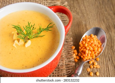 Lentil cream soup with cheese and dill  on napkin and wooden background, horizontal close up
