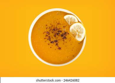Lentil cream soup with lemon slices with yellow background