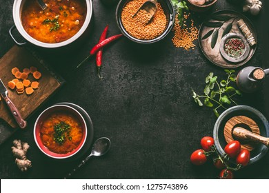 Lentil dishes food background. Lentil soup with cooking ingredients on dark rustic kitchen table background, top view. Healthy vegan food concept. Blank cutting board and vegetarian lentil meal