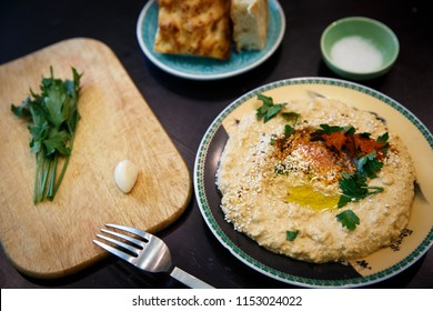 Lentil hummus in bowl and pita bread on wooden table