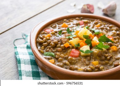 Lentil soup in a bowl on wooden background