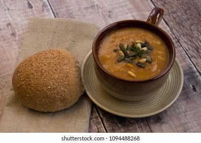 Lentil Soup with A Bread Roll & Garnish of Pumpkin Seeds and Pine Nuts.