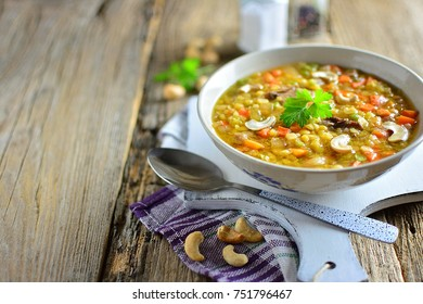 Lentil soup with cashew in a plate, old wooden rustic background, copy space