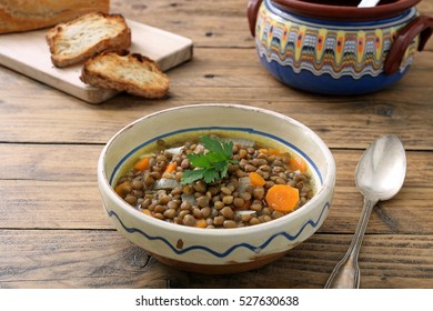 Lentil soup in ceramic bowl on rustic kitchen table background