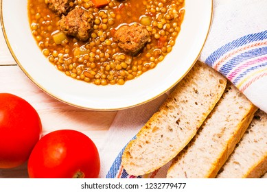 Lentil soup with fricandel, tomatoes and bread on wooden background