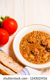 Lentil soup with fricandel, tomatoes and bread on wooden background. Copy space