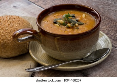 Lentil Soup with pumpkin seeds and pine nut garnish and a sprig of thyme