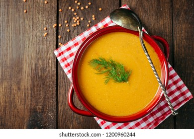 Lentil soup, red ceramic saucepan, wooden background, legumes, home cooking