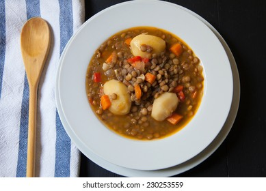 lentil soup served on white bowl with wood spoon