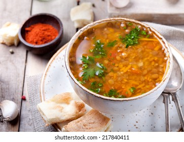 Lentil soup with smoked paprika and bread in a ceramic bowl on a wooden background