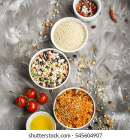 Lentils, bulgur, wheat cereal, dried tomatoes and onion with olive oil on a marble background. Ingredients for dinner. Top view. Ready-mix for soup