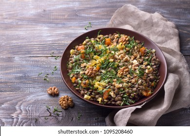 Lentils with dried apricots, nuts, fried onions and parsley. mshosh of lentils, an Armenian dish. delicious healthy national dish. on a wooden table. free space