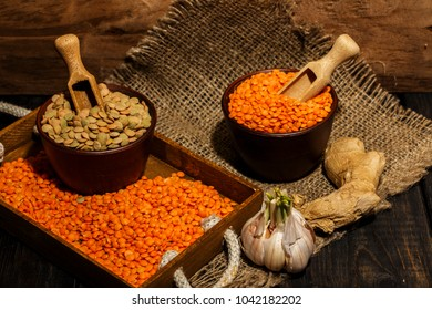 Lentils seeds on a wooden table with sackcloth. Seeds of red and green dietary supplements of lentils. Useful lentils of the legume family.