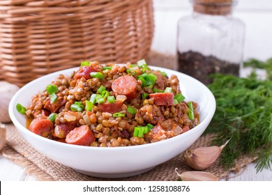 Lentils with smoked sausages in a white plate on the table