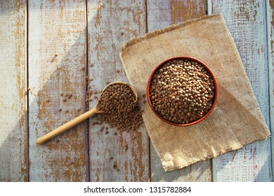 Lentils and spoon in wooden bowl close up on old table