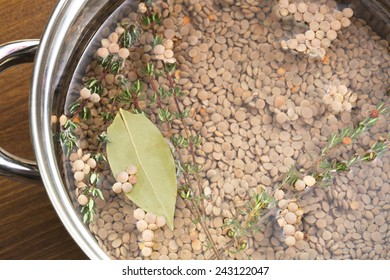 Lentils, thyme and bay leaf in pot with water, ready for cooking.