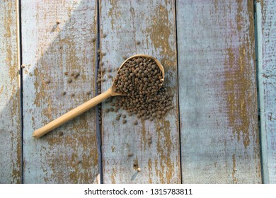 Lentils in wooden spoon closeup on old table