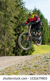 Lenzerheide, GR / Switzerland, - 12 October, 2019: downhill mountain biker jumping high and riding hard in Lenzerheide in the Swiss Alps