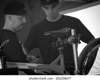 LEOGANG, AUSTRIA - JUNE 14, 2014: Sam Hill (r) of CRC/Nukeproof is seen with team mechanic Jacy Shumilak in the team's pit before Qualification of the UCI Downhill Mountain Bike World Cup in Leogang.