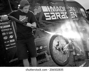 LEOGANG, AUSTRIA - JUNE 15, 2014: A technician with Madison Saracen Factory Team cleans one of the team's bike after the final of the UCI Downhill Mountain Bike World Cup in Leogang, Austria.
