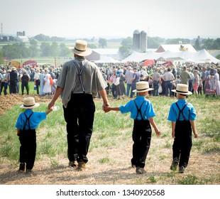 LEOLA, PA/USA - JUNE 30, 2017: Amish fathers walks his three sons to view the Horse Progress Days  activities in Leola, Pensylvania on June 30, 2017.