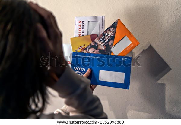 Leon, Spain. Circa November 2019. Unidentifiable woman looks at different envelopes containing advertisement and ballots for the 2019 Spanish presidential election; selective focus.