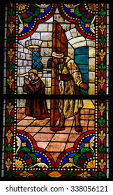 LEON, SPAIN - JULY 17, 2014: Stained glass window depicting a praying Catholic Saint held captive by Moors, in the cathedral of Leon, Castille and Leon, Spain.