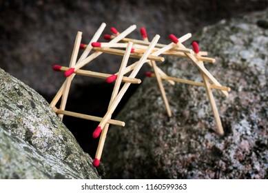 leonardo da vinci's self supporting bridge built from matches between big rocks, selected focus, narrow depth of field
