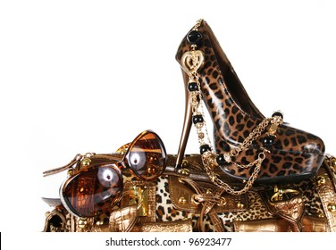 leopard handbag, shoe, sunglasses and golden necklace isolated on white
