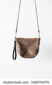 Leopard print crossbody bag hanging in front of white background, isolated, copy space