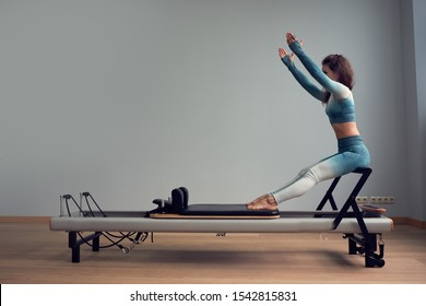 leotard workout pilates training. athletic pilates reformer exercises. pilates machine equipment. young asian woman pilates stretching sport in reformer bed instructor girl in a studio