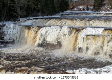 Lepreau Falls, New Brunswick, Canada, in winter. The falls are partially frozen, golden water flows over the rest.