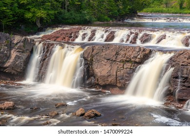 Lepreau Falls in New Brunswick, Canada. Long exposure softens the waterfall as it flows over brown rock. Trees next to the river, bright sunny day.