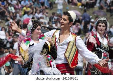 "LEPUSHE, ALBANIA - AUGUST 11: a young couple in albanian costume performs a courtship dance. The beautiful girl is the winner of ""Miss Mountain 2012"" in Lepushe, commune of Kelmend. Shot in 2012"
