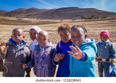 LERIBE, LESOTHO - AUGUST 10, 2016: Friendly children walk home from school in beautiful winter scenery of south Africa's mountain kingdom; free, compulsory universal primary education began in 2000