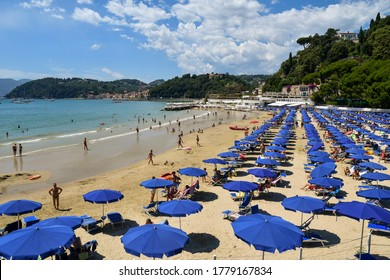 Lerici, La Spezia / Italy - June 21 2020: Elevated view of the sandy beach with sun umbrellas and deck chairs on the sea shore of the Gulf of the Poets with the coastline in the background in summer